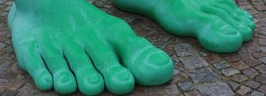 Close up of two massive giant green statue's feet