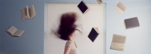 A woman with books flying around her head
