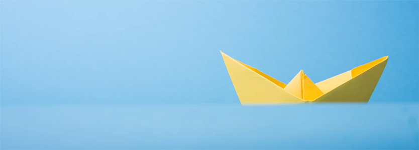 A yellow origami boat on a blue background