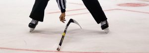 An ice hockey referee bending down to pick up a hockey stick